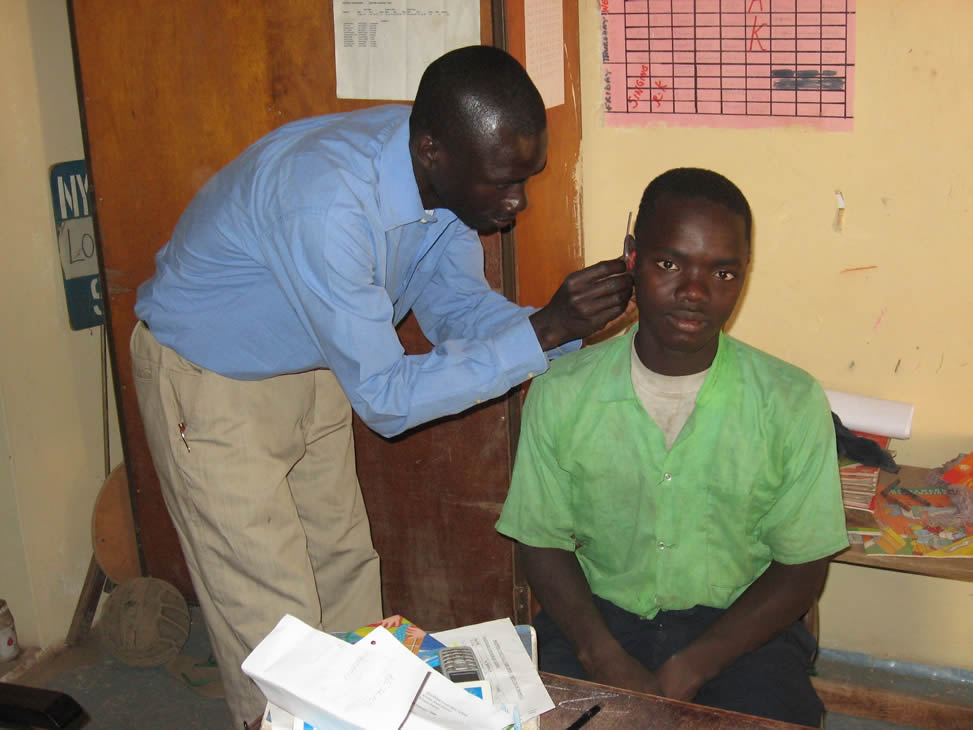 Itinerant Teacher Andrew Jatta fitting hearing aid to pupil in mainstream school